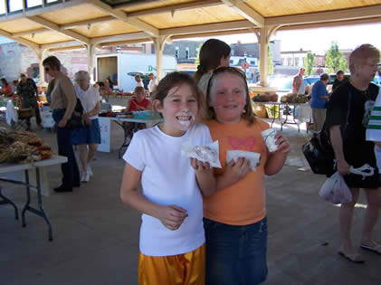 2 young girls enjoy snacks and drinks at the Farmers' Market